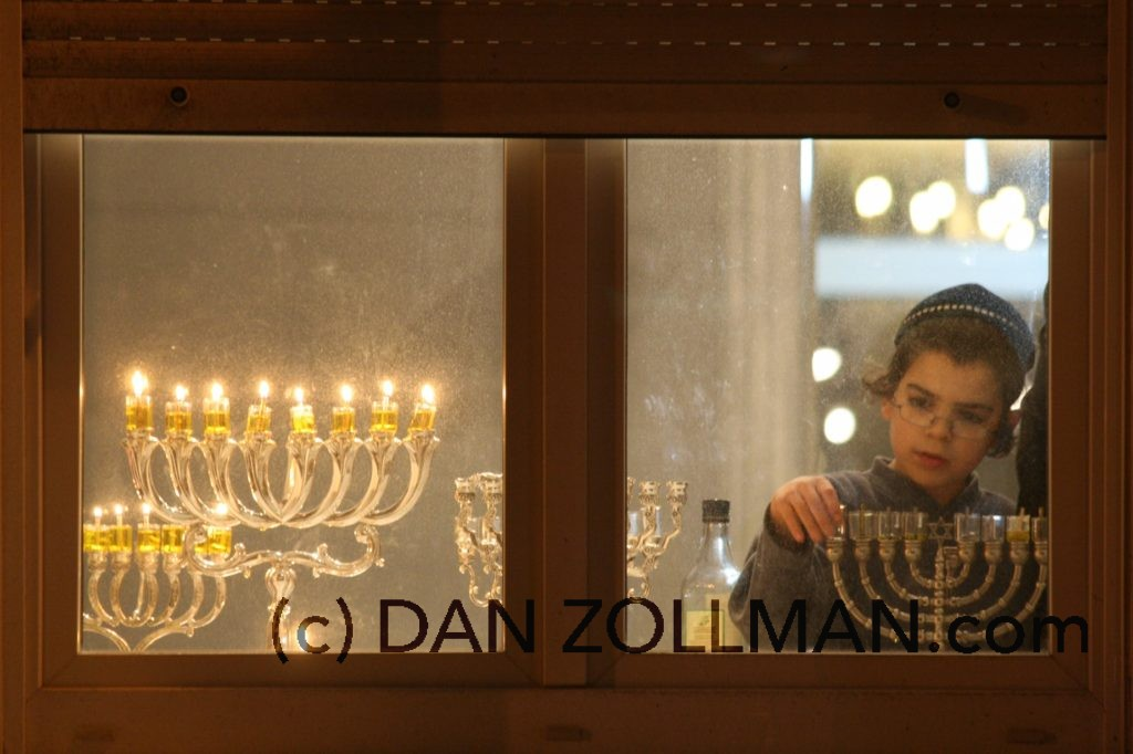 jongen doet de kaarsen van de menora aan, sabba