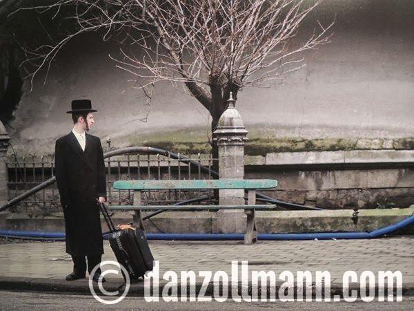 eenzame man met hoed en rolkoffer, op de achtergrond de bedding van Antwerpen Centraal